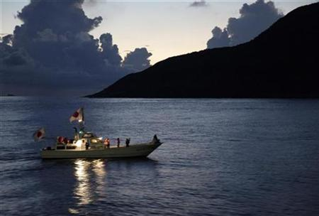 A fishing boat with hoisted Japanese national flags, sails around a group of disputed islands known as Senkaku in Japan and Diaoyu in China in the East China Sea September 2, 2012. REUTERS/Chris Meyers