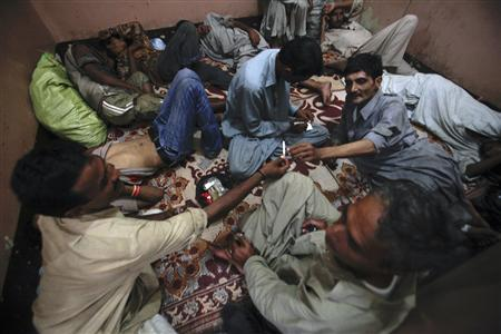 A drug addict passes a cigarette to another addict as they rest in a room of the Hope Rehabilitation Centre in Karachi in this September 8, 2011 file photo. To match Special Report PAKISTAN-KINGPIN/ REUTERS/Akhtar Soomro
