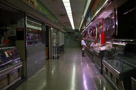 A man shops at a butcher's store in a local market in Madrid September 4, 2012. REUTERS/Susana Vera
