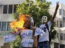 A Palestinian protester wearing a Guy Fawkes mask gestures as he stands near a burning effigy of Palestinian Prime Minister Salam Fayyad during a demonstration against the high cost of living, in the West Bank city of Hebron in this September 4, 2012 file photo. REUTERS/Mussa Qawasma/Files