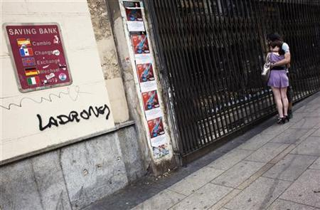 A couple looks at the window of a closed store next to graffiti that reads ''Thieves'' on the wall of the savings bank Cajastur in Madrid June 11, 2012. REUTERS/Susana Vera