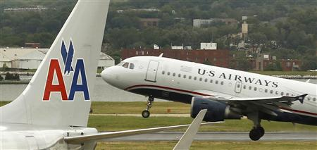 A US airways plane takes off behind an American Airlines jet at Ronald Reagan National Airport in Washington in this April 23, 2012 file photo. REUTERS/Kevin Lamarque/Files