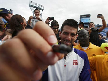 Novak Djokovic of Serbia signs autographs after defeating Stanislas Wawrinka of Switzerland in their men's singles match at the U.S. Open tennis tournament in New York September 5, 2012. REUTERS/Eduardo Munoz