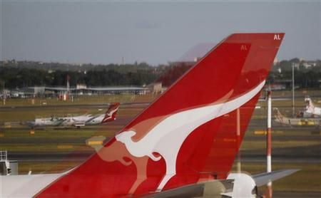The tail of a Qantas 747 is reflected in a window at Kingsford Smith international airport in Sydney May 22, 2012. REUTERS/Daniel Munoz