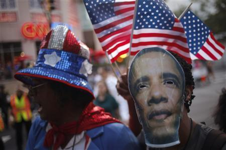 A supporter of U.S. President Barack Obama wears a mask with his image while waving U.S. flags through uptown Charlotte, the site of the Democratic National Convention in North Carolina September 5, 2012. REUTERS/Adrees Latif