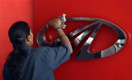 A worker cleans a logo of Mahindra & Mahindra, India's largest utility vehicles maker, inside their showroom in Chennai April 12, 2011. REUTERS/Babu (INDIA - Tags: BUSINESS TRANSPORT)