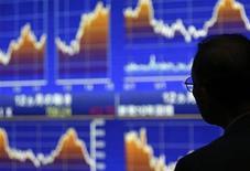 Мужчина смотрит на экраны с графиками японских фондовых котировок возле брокерской конторы в Токио, 5 июня 2012 года. Прогноз для крупных развитых экономик ухудшился в последние месяцы, так как кризис еврозоны достиг сердцевины региона, заявила в четверг Организация экономического сотрудничества и развития. REUTERS/Toru Hanai