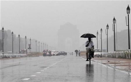 A man holds an umbrella whilst cycling as it rains in New Delhi August 24, 2012. REUTERS/Adnan Abidi