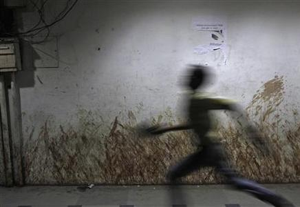 A boy runs past a wall stained with tobacco spit along a street in New Delhi August 26, 2012. Ten Indian states have banned a popular form of chewing tobacco in a major policy shift that may save millions of lives and strike a blow at the global tobacco industry, already reeling from new anti-smoking laws around the world. But an estimated 65 million Indians use ''gutka'' - a heady form of chewing tobacco made of crushed betel nut, nicotine and laced with thousands of chemicals - and furious manufacturers are fighting to have the bans overturned. Picture taken August 26, 2012. REUTERS/Mansi Thapliyal