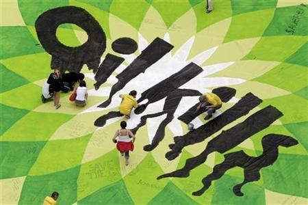 Greenpeace activists paint over a banner with the British Petroleum (BP) logo at St. Stephen's square in Vienna, during a protest against the Deepwater Horizon gulf oil spill in the Gulf of Mexico in this July 7, 2010 file photo. REUTERS/Lisi Niesner/Files