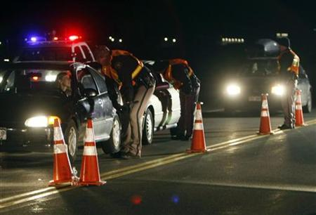 Jefferson County Sheriff Department officers ask drivers if they have been drinking while smelling for alcohol at a mobile Driving Under the Influence (DUI) checkpoint in Golden, Colorado late April 12, 2008. REUTERS/Rick Wilking