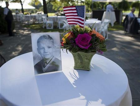 A photograph of Neil Armstrong as a young man is displayed on a table during a memorial service celebrating the life of Armstrong at the Camargo Club in Cincinnat, Ohio August 31, 2012 in this NASA handout photo. REUTERS/NASA/Bill Ingalls/Handout.