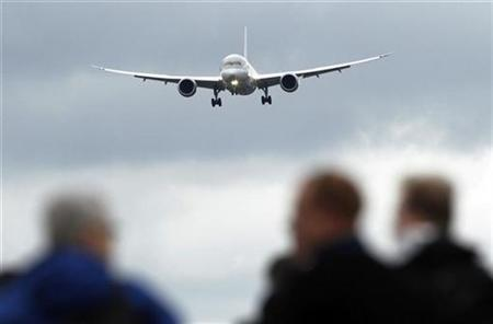 Spectators watch a Boeing 787 Dreamliner performing a display flight at the Farnborough Airshow 2012 in southern England July 9, 2012. REUTERS/Luke MacGregor