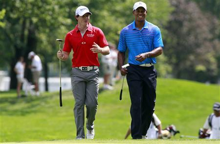 Rory McIlroy (L) of Northern Ireland talks with Tiger Woods of the U.S. as they approach the first green during round one of the BMW Championship golf tournament in Carmel, Indiana September 6, 2012. REUTERS/Brent Smith