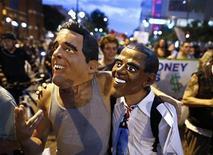 Демонстранты в масках Ромни и Обамы на улице Шарлотта, Северная Каролина 6 сентября 2012. Президент США Барак Обама попросил американцев проявить терпение, восстанавливая слабую экономику, призвал дать ему еще один шанс на посту главы государства и решительно отверг меры возрождения роста, предложенные республиканцем Миттом Ромни. REUTERS/John Adkisson