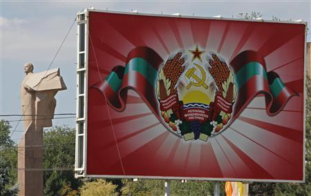 A statue of communist leader Lenin is seen near a poster with the official coat of arms in Tiraspol, in Moldova's self-proclaimed separatist Transdniestria August 31, 2012. REUTERS/Gleb Garanich