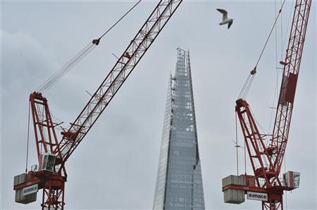 A gull flies near construction cranes with the Shard building seen behind in London August 24, 2012. REUTERS/Toby Melville