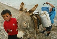 Киргизские мальчики набирают воду на озере Сон-Куль в горах Тянь-Шаня 24 июля 2005. Споры вокруг использования водных ресурсов Центральной Азии рискуют вылиться в конфликты в постсоветском регионе, предупредил соседей, планирующих строительство гидротехнических плотин, президент Узбекистана Ислам Каримов. REUTERS/Stringer