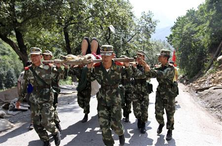 Soldiers carry an injured person with a stretcher towards safer area after two earthquakes hit Zhaotong, Yunnan province, September 7, 2012. REUTERS/Stringer