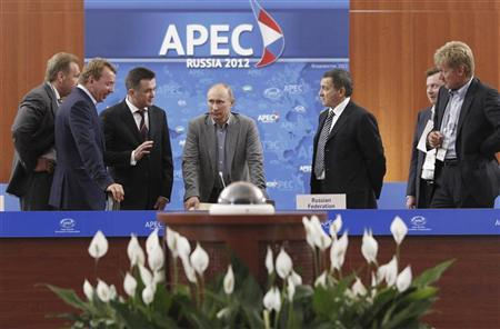 Russia's President Vladimir Putin (C) visits the international press centre of the Asia-Pacific Economic Cooperation (APEC) summit in Vladivostok September 6, 2012. REUTERS/Mikhail Klimentyev/Ria Novosti/Pool
