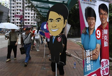 Passersby look on as supporters of candidate Gary Chan (R, on banner), from the pro-China Democratic Alliance for the Betterment of Hong Kong, carry a cartoon cut-out of him during an election campaign in Hong Kong September 7, 2012. REUTERS/Bobby Yip