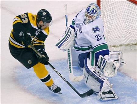 Boston Bruins left wing Brad Marchand scores under the leg of Vancouver Canucks goalie Cory Schneider in the first period action during their NHL hockey game in Boston, Massachusetts January 7, 2012. REUTERS/Adam Hunger
