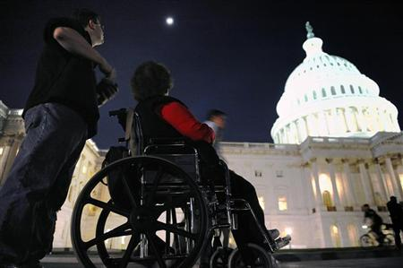A woman in a wheelchair and her son are just a few of thousands of protestors remain late in the evening after a 'Kill the Bill' rally against US President Barack Obama's health care legislation, on the grounds of the US Capitol in Washington, March 20, 2010. REUTERS/Jonathan Ernst