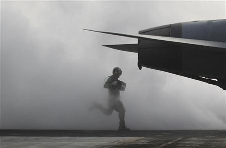 A flight deck crew runs as he prepares a U.S. Navy F/A-18F Super Hornet for take-off on the U.S. Navy's USS George Washington aircraft carrier during a joint military drills between the U.S. and South Korea in the West Sea November 30, 2010. REUTERS/Kim Kyung-Hoon