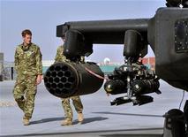 O príncipe Harry é visto próximo do helicóptero Apache, com um membro não identificado de seu esquadrão, no Afeganistão. 07/09/2012 REUTER/John Stillwell/POOL