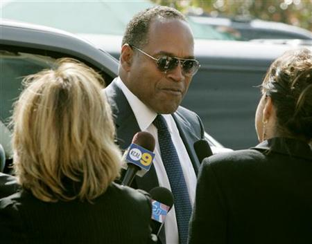 Former NFL star and actor O.J. Simpson talks with reporters as he arrives for the funeral of attorney Johnnie Cochran in Los Angeles, April 6, 2005. REUTERS/Fred Prouser