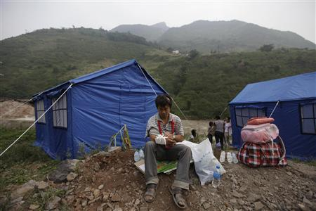A injured survivor adjusts his bandages in front of tents in Luozehe town after two earthquakes hit Yiliang, Yunnan province September 8, 2012. Rescuers in southwestern China tried on Saturday to reach remote communities rocked by back-to-back earthquakes that killed at least 89 people and damaged many thousands of buildings, state media reported said. Shallow 5.6 magnitude quakes struck an impoverished, mountainous part of the country with poor infrastructure and communications on Friday and the death toll could rise as news trickled in from cut-off areas, the Xinhua news agency said. REUTERS/Jason Lee