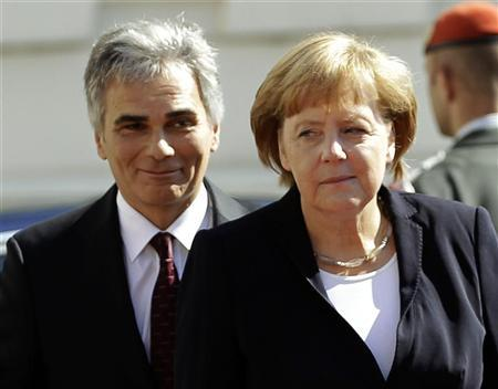 Austrian Chancellor Werner Faymann and German Chancellor Angela Merkel walk to review the guard of honour prior to a meeting in Vienna September 7, 2012. REUTERS/Leonhard Foeger