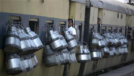 Milk containers hang from the windows of a passenger train in Ghaziabad on the outskirts of New Delhi March 14, 2012. REUTERS/Parivartan Sharma/Files