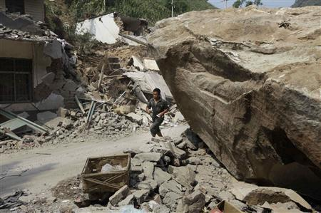 A man runs past a huge stone and damaged houses in Luozehe town, after two earthquakes hit Yiliang, Yunnan province September 9, 2012. Rescuers in southwestern China tried on Saturday to reach remote communities rocked by earthquakes that killed at least 80 people and damaged thousands of buildings, more than 800 people were injured, state media reported. REUTERS/Jason Lee
