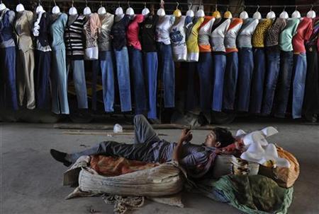 A vendor lies on the ground as he waits for customers in Kashgar, Xinjiang Uighur Autonomous Region, September 9, 2012. REUTERS/Stringer