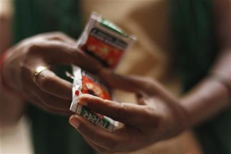 A woman holds packets of gutka on a street in New Delhi August 28, 2012. REUTERS/Mansi Thapliyal