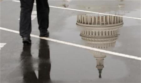 The dome of the U.S. Capitol Building is reflected in a puddle on a rainy morning in Washington February 2, 2012. REUTERS/Kevin Lamarque/Files