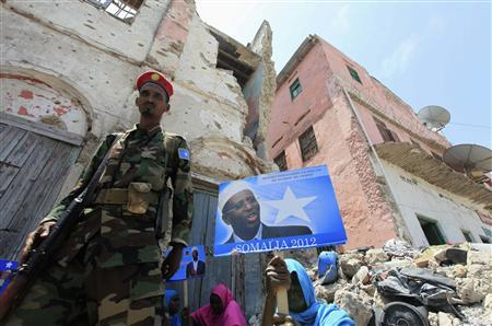 A government soldier walks past a woman holding a campaign poster of Somalia's President Sheikh Sharif Ahmed in Mogadishu, September 9, 2012. The presidential election will be held on September 10. REUTERS/Feisal Omar