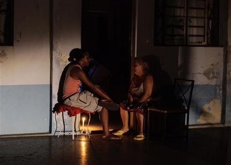 People sit at the door of their home during a power blackout in Havana September 9, 2012. A large swath of Cuba was plunged into darkness on Sunday night in a widespread power failure, the cause of which was not disclosed. Electricity went out from the city of Ciego de Avila in southeastern Cuba all the way to Havana, 250 miles (400 km) to the northwest, and beyond to the westernmost province of Pinar del Rio. Picture taken September 9, 2012. REUTERS/Desmond Boylan