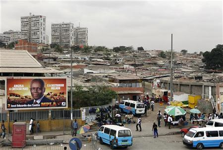 An election poster of the ruling MPLA party with the housing in the backdrop is seen in the capital Luanda, August 30, 2012. REUTERS/Siphiwe Sibeko