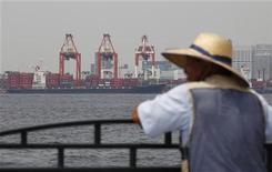 Мужчина смотрит на море, по которому проплывает грузовое судно, в токийском порту, 25 июля 2012 года. Рост экспорта Китая не оправдал прогнозов в августе, в то время как импорт неожиданно снизился, усложнив задачу поддержания роста властям на фоне ослабления внутреннего спроса и ухудшения прогноза мировой экономики. REUTERS/Yuriko Nakao