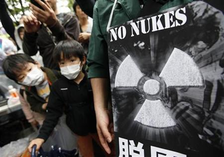 Boys stand next to an anti-nulcear banner at a rally in Tokyo May 7, 2011. REUTERS/Kim Kyung-Hoon