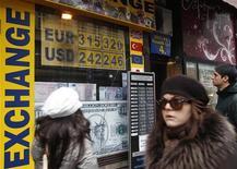Люди проходят мимо обменного пункта в Будапеште, 4 января 2012 года. Евро снижается к доллару, но пока близок к максимуму четырех месяцев, так как рынки рассчитывают на стимулирующие меры ФРС США. REUTERS/Laszlo Balogh