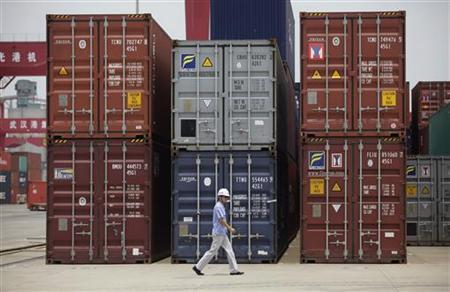 An employee walks past shipping containers at a port near Yangtze River in Wuhan, Hubei province July 10, 2012. REUTERS/Stringer