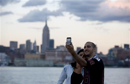 With the skyline of New York behind them, a couple takes a picture of themselves from a pier in Hoboken, New Jersey, September 9, 2012. New York will mark the 11th anniversary of the attack on the World Trade Center with ceremonies on September 11. REUTERS/Gary Hershorn