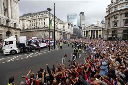 A flatbed truck transporting members of Britain's Olympic and Paralympic teams travels past well wishers during a parade through the city of London September 10, 2012. REUTERS/Andrew Winning