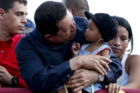 Venezuelan President and Presidential candidate Hugo Chavez carries a girl during a campaign rally in Charallave in the state of Miranda outside Caracas September 9, 2012. Venezuela will vote in the presidential election in October. REUTERS/Jorge Silva