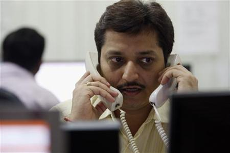 A trader speaks on phones while trading at a stock brokerage in Mumbai March 22, 2010. REUTERS/Arko Datta/Files