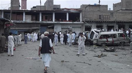 Tribesmen, security officials and the media gather at the site of a bomb attack in the main town of Parachinar, located in Pakistan's Kurram region, September 10, 2012. A car bomb exploded at a market in northwest Pakistan on Monday, killing at least 14 people and wounding 45, officials said. REUTERS/ Javed Hussain