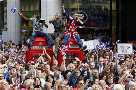 Spectators watch a parade of Britain's Olympic and Paralympic athletes make its way through London September 10, 2012. Tens of thousands of Britons took to the streets of London on Monday to cheer Olympic and Paralympic athletes, celebrating a summer of spectacular sport that surprised even the most optimistic by lifting the host nation's mood. REUTERS/Stefan Wermuth